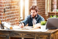 Architect Working With Blueprint While Sitting stock photos