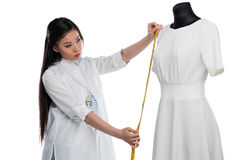 Concentrated young asian dressmaker measuring stylish white dress on dummy. Isolated on white Stock Photography