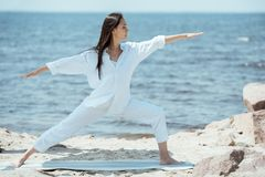 concentrated young asian woman practicing yoga in virabhadrasana royalty free stock photos