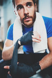 Concentrated Young athlete tying black boxing bandages.Boxer man prepairing before kickboxing training in gym. Blurred. Background. Vertical royalty free stock images