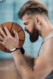 Concentrated young basketball player holding ball Stock Photography