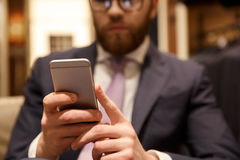 Concentrated young bearded businessman chatting by phone. Stock Images