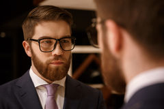 Concentrated young bearded businessman looking at mirror. Photo of concentrated young bearded businessman standing indoors. Looking at mirror royalty free stock photography