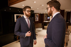 Concentrated young bearded businessman standing indoors stock photos