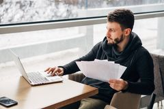 Concentrated Young Bearded Businessman Wearing Black Tshirt Working Laptop Urban Cafe. Man Sitting Wood Table Looking Through Window.Coworking Process Business Royalty Free Stock Image
