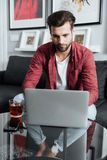 Concentrated young bearded man using laptop computer drinking tea Royalty Free Stock Photo