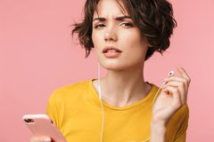 Concentrated young beautiful woman posing isolated over pink wall background listening music with earphones using mobile phone try royalty free stock photos