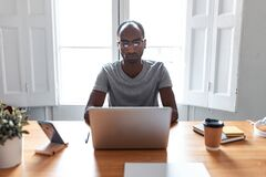 Free Concentrated Young Black Business Man Working With Laptop In The Office Royalty Free Stock Image - 170375986