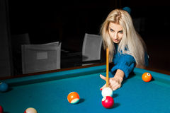 Concentrated young blonde billiard player in game process Royalty Free Stock Photo