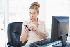 Concentrated young blonde businesswoman texting with her mobile phone Royalty Free Stock Image