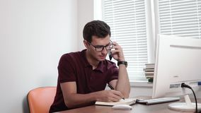 Concentrated young businessman in glasses writing notes while talking on mobile phone with client at the office. Shot in. 4k stock footage
