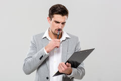 Concentrated young businessman planning and writing in clipboard Stock Photography