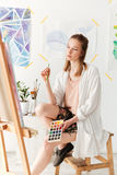 Concentrated young caucasian lady painter at workspace Stock Photo