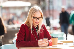 Concentrated young caucasian lady sitting in cafe Stock Photo