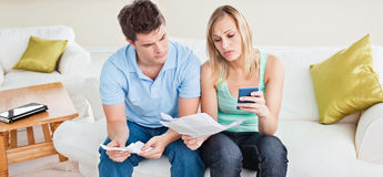 Concentrated young couple calculating bills Stock Images
