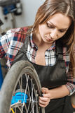 Concentrated young craftswoman using the tire gauge Stock Photography