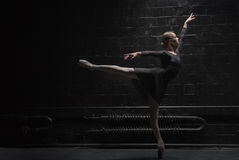 Concentrated young dancer training near the dark wall Royalty Free Stock Images