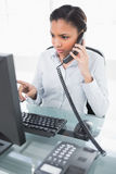 Concentrated young dark haired businesswoman answering the telephone Royalty Free Stock Photo