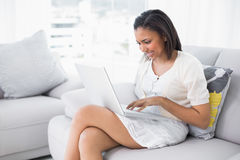 Concentrated young dark haired woman in white clothes typing on a laptop Royalty Free Stock Photo