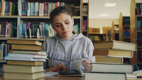 Concentrated young female student reading books and writing in notebook during working at school project in university. Library indoors stock video footage