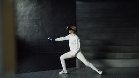 Concentrated fencer woman practice fencing exercises using VR headset and training simulator competition game indoors. Concentrated young fencer woman practice Stock Photo