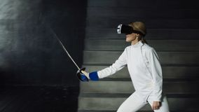 Concentrated fencer woman practice fencing exercises using VR headset and training simulator competition game indoors Stock Photo