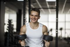 Concentrated young fitness man working out with dumbbells in gym.  royalty free stock image
