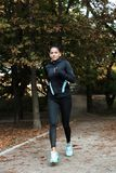 Concentrated young fitness woman jogging at the park stock images