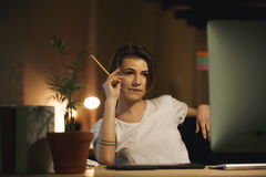 Concentrated young lady designer holding pencil. Stock Photo