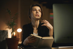 Concentrated young lady designer reading book. Stock Photography