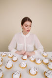 Concentrated young lady posing while sitting near cupcake Royalty Free Stock Photos