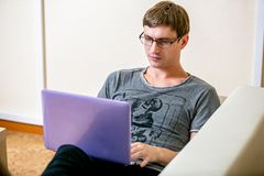 Concentrated young man with glasses working on a laptop in a home office. Prints on the keyboard and scans the text on the display stock image