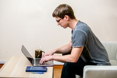 Concentrated young man with glasses working on a laptop in a home office. Type on a keyboard and scrolls text on the display. side royalty free stock photography