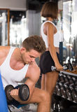 Concentrated young man making biceps curls in gym. Concentrated young men making biceps curls using heavy dumbbells in gym Royalty Free Stock Photography