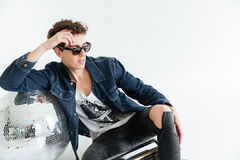 Concentrated young man near disco ball and boombox. Picture of concentrated young man wearing sunglasses sitting  over white background near disco ball and Stock Photos