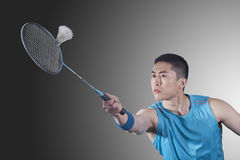 Concentrated Young man playing badminton, hitting Royalty Free Stock Images