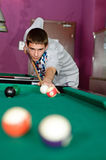 Concentrated young man playing snooker. Photo of young man during snooker game royalty free stock photo