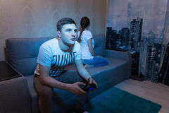 Concentrated young man playing a video game and ignore his offen. Concentrated young men playing a video game holding a console sitting on the sofa at home Royalty Free Stock Photos