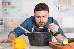 Concentrated young man preparing food at home. Man is cooking in his kitchen and adding ingredient royalty free stock photos