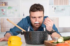 Concentrated young man preparing food at home royalty free stock photo
