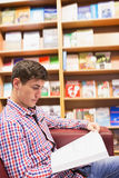 Concentrated young man reading book in library Stock Photo