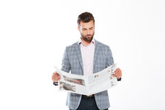 Concentrated young man reading gazette Royalty Free Stock Image