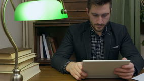 Concentrated young man sitting at desk with books using digital tablet stock footage