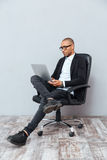 Concentrated young man sitting in office chair and using laptop Royalty Free Stock Images