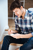 Concentrated young man sitting and writing in notepad at home. Concentrated young man in checkered shirt sitting and writing in notepad at home Stock Image