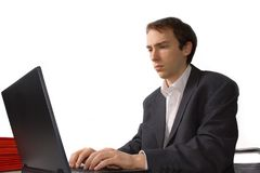 Concentrated young man works on laptop. Isolated over white Stock Photography