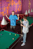 Concentrated young men playing snooker. Photo of young men during snooker game stock photography
