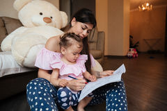 Concentrated young mother with daughter drawing in colouring book Royalty Free Stock Image
