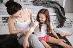 Concentrated young mother furnishing first aid help at home Stock Image