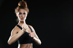 Concentrated young sports lady boxer. Picture of concentrated young sports lady boxer standing over black background and posing. Looking at camera royalty free stock photo